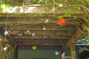 Glass ornaments hang from our entry pergola